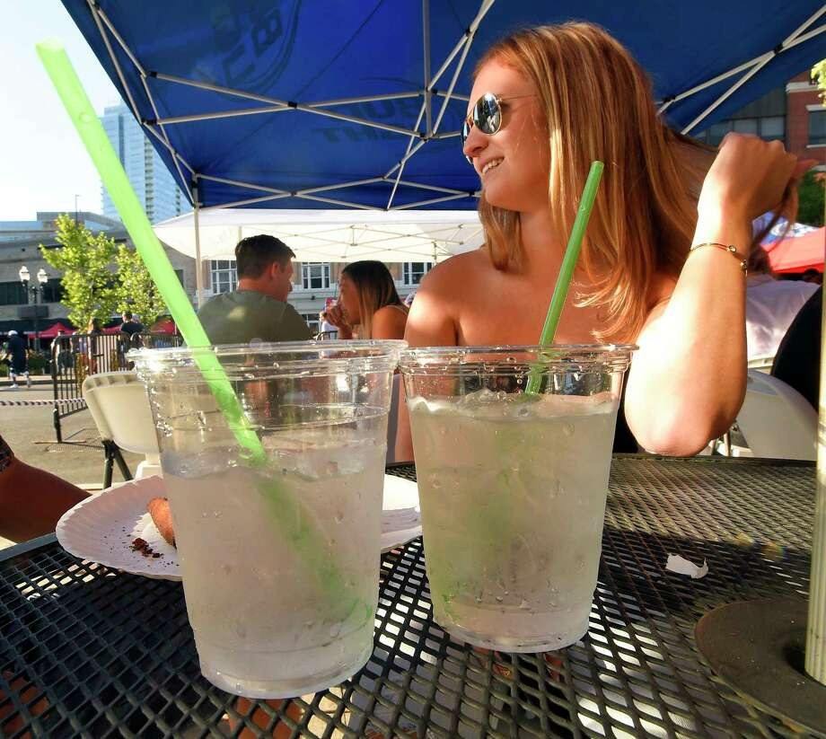 Kelsey Marioni of Stamford relaxes outside having a drink with a friend at Teena's Apizza, a Stamford restaurant which opened last month, that only uses recyclable products, including totally compostable staws made from plant material, shown in a photograph taken on July 19, 2018 in Stamford, Connecticut. Photo: Matthew Brown, Hearst Connecticut Media / Stamford Advocate