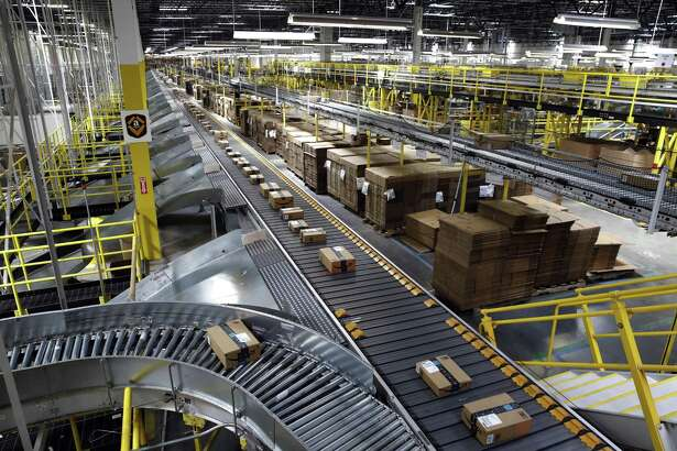 In this Aug. 3, 2017, file photo, packages ride on a conveyor system at an Amazon fulfillment center in Baltimore.Amazon is by far the largest marketplace for both new and used books the world has ever seen, and is also one of the most inscrutable. The retailer directly sells some books, while others are sold by third parties, and wild pricing happens with the latter.