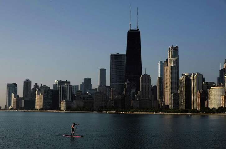 Chicago offers a cautionary tale to a younger city like Houston about ensuring that growth is financially sustainable.  A paddle boarder coasts along the smooth surface of Lake Michigan with the downtown skyline in the background Wednesday morning, Aug. 20, 2014, in Chicago. (AP Photo/Kiichiro Sato)