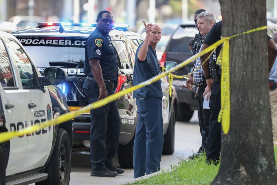 A man in medical scrubs talks to Homicide detective and Houston Police officers at the scene where a doctor from Houston Methodist Hospital died after being shot near the Texas Medical Center Friday, July 20, 2018, in Houston.