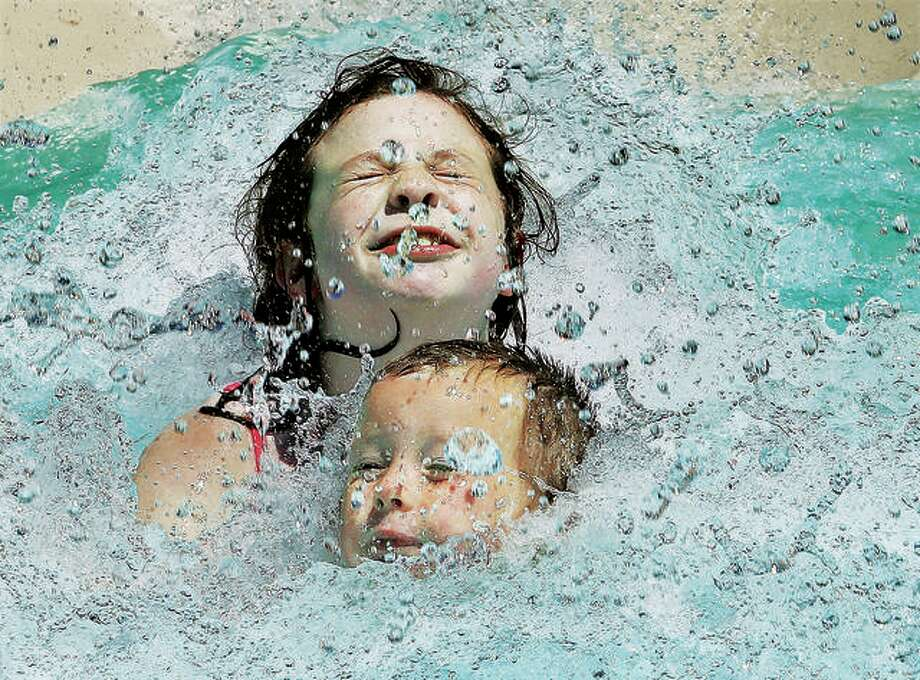 In this 2016 file photo, two kids try to keep their heads above water as they hit the bottom of the water slide at the Wood River Aquatic Center. The city moved forward with the removal of the Aquatic Center this week, approving sale of equipment and supplies from the pool. Photo:       John Badman | The Telegraph