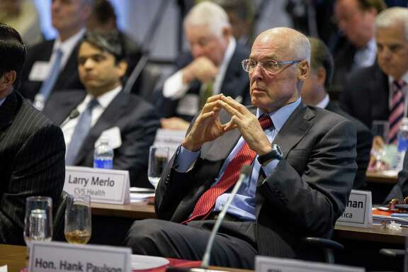 In this Sept. 16, 2015, photo, former Treasury Secretary Henry Paulson listens as President Barack Obama speaks to business leaders at the quarterly meeting of the Business Roundtable in Washington to renew his calls for increased spending in infrastructure, education and scientific research. Three officials including Paulson who played vital roles in combating the 2008 financial crisis say they worry that the painful lessons from the banking systems near-collapse a decade ago may be forgotten.