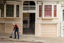 Property owner Noni Richen sweeps the leaves in front of the four-unit rent-controlled apartment she owns in the Western Addition neighborhood of San Francisco, Calif. Thursday, July 19, 2018.