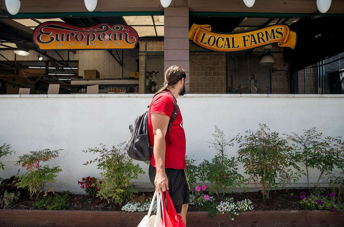 A shopper walks past the front entrance of Milk Pail Market n Mountain View, Calif. Wednesday, July 18, 2018.