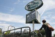 A woman retrieves a cart before shopping for groceries at Milk Pail Market in Mountain View, Calif. Wednesday, July 18, 2018.