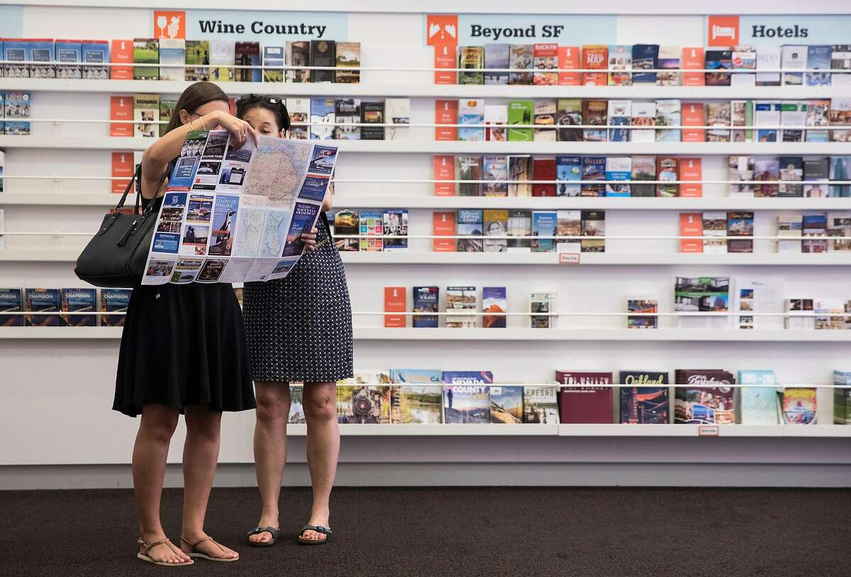 Two French tourists look over a map of San Francisco while at the San Francisco Visitor Information Center near Union Square in San Francisco, Calif. Friday, July 20, 2018.