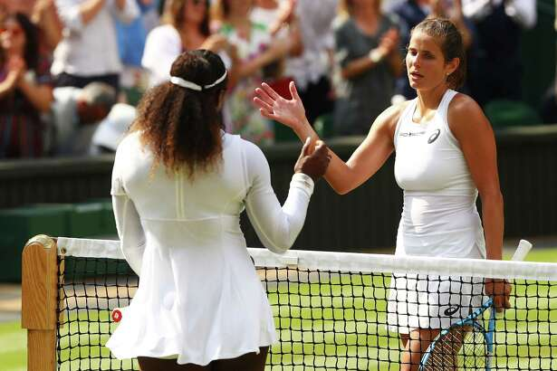 Serena Williams, left, shakes hands with Julia Goerges after their semifinal match at Wimbledon.