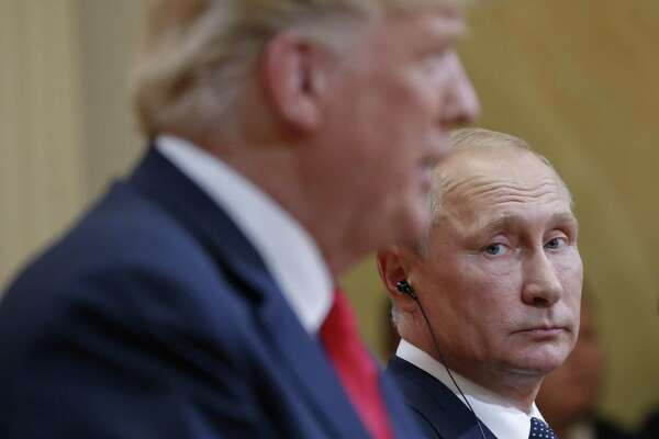 Russian President Vladimir Putin, right, looks over towards U.S. President Donald Trump, left, as Trump speaks during their joint news conference at the Presidential Palace in Helsinki, Finland, Monday.