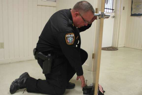 Splendora ISD Police Chief Rex Evans demonstrates how door stops can be slipped under the bottom of a door and then a pin slipped into place to prevent the door from being forced open during an active shooter situation.