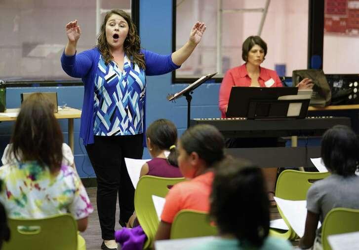 Choir co-directors Alyssa Hunsucker Avenatti, left, and Rebecca Morgan lead Boys and Girls Club kids in song during a three-week choir camp hosted by the Children's Chorus of San Antonio.