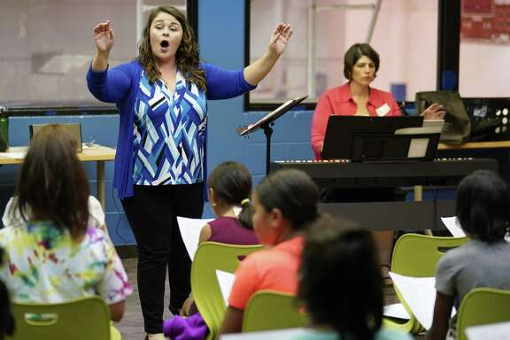 Choir co-directors Alyssa Hunsucker Avenatti, left, and Rebecca Morgan lead Boys and Girls Club kids in song during a three-week choir camp hosted by the Children's Chorus of San Antonio.