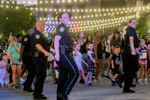 """Alton Police Department Detective Pfc. Emily Hejna, front, dances with colleagues and dozens of children who showed up to West Third Street Thursday night for one of several tapings of the department's version of a """"Lip Sync Challenge"""" video."""