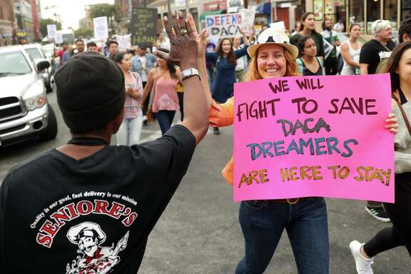Allison Banks of Berkeley high fives a man as a protest march heads down Durant Avenue during pro-DACA rally in Berkeley, Calif., on Sept. 5. A reader says the public is forgetting the Dreamers.