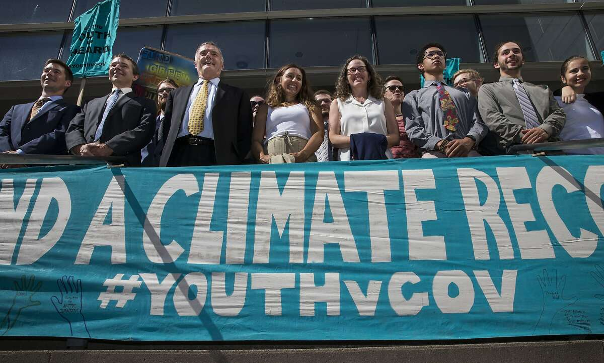 FILE - In this July 18, 2018, file photo, lawyers and youth plaintiffs lineup behind a banner after a hearing before Federal District Court Judge Ann Aiken between lawyers for the Trump Administration and the so called Climate Kids in Federal Court in Eugene, Ore. The lawsuit filed by young activists who say the government is failing to protect them from climate change is still alive. In San Francisco on Friday, July 20, 2018, the 9th U.S. Circuit Court of Appeals rejected the government's second request for an order directing a lower court to dismiss the case. (Chris Pietsch/The Register-Guard via AP, File)