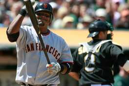 San Francisco Giants' Juan Uribe reacts after striking out for the third out in the eighth inning as Oakland Athletics' Kurt Suzuki walks back to the dugout in s baseball game in Oakland, Calif., Saturday, May 22, 2010. (AP Photo/Darryl Bush)
