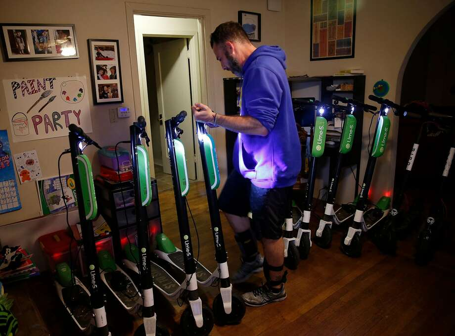 David Padover lines up scooters from companies including Lime and Bird for charging in his San Jose living room. Photo: Photos By Josie Lepe / Special To The Chronicle