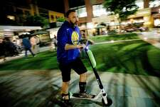 David Padover, who is a Juicer for Lime-S, rides a scooter he collected at Santana Row, while scooter hunting in San Jose, California on July16, 2018. (Josie Lepe/Special to the Chronicle)