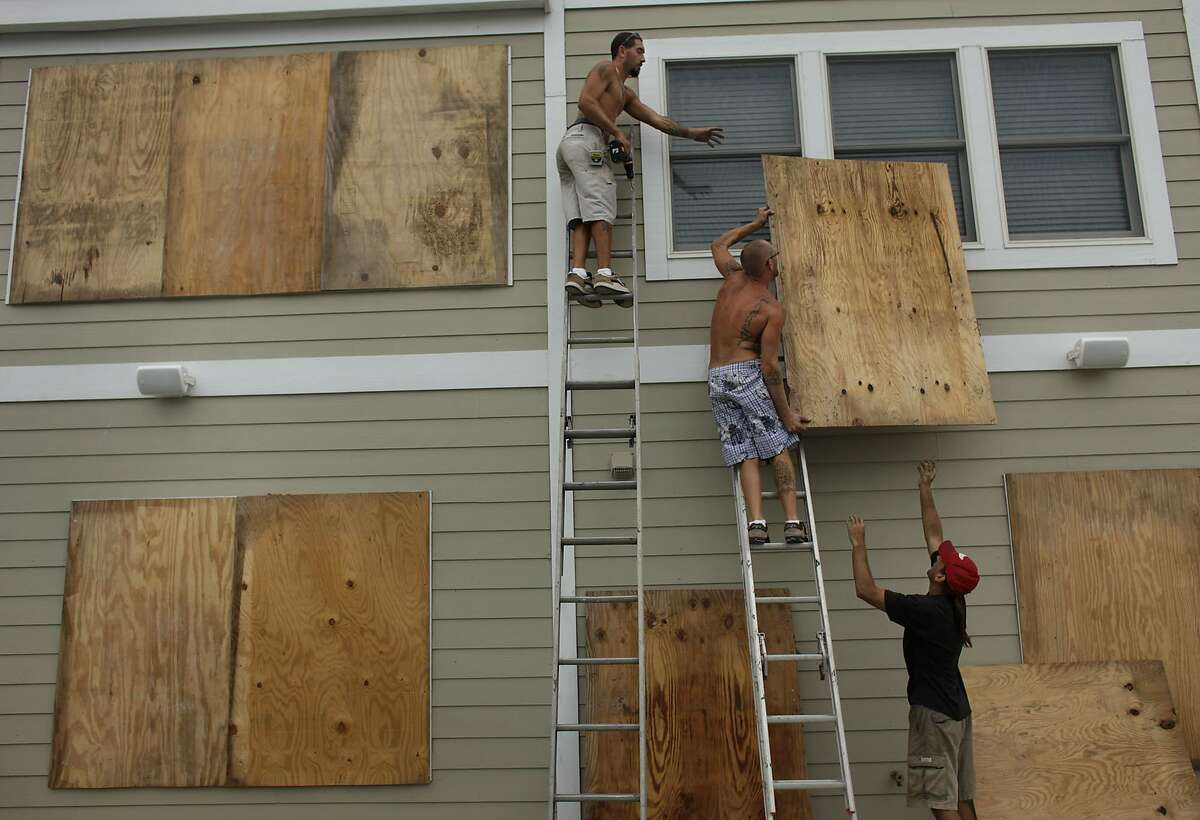 Justin Hartleben, left, Jared Hartleben, center, and Kevin Hall, with Caswell Construction, board up a home in Nags Head, NC Thursday, Sept. 2, 2010, in preparation for the possible landfall of Hurricane Earl. (AP Photo/The Virginian-Pilot, Stephen M. Katz)