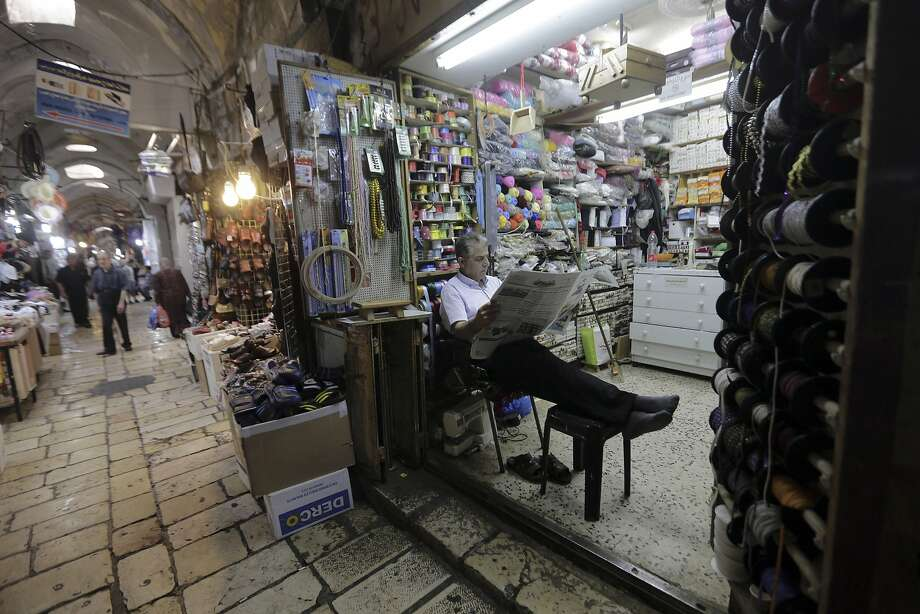 In this Wednesday, July 11, 2018 photo, a shopkeeper waits for customers in the Muslim Quarter of the Old City in Jerusalem. A half-a-billion-dollar Israeli plan to develop Palestinian areas of east Jerusalem and hoist tens of thousands of residents out of poverty is getting a cool reception from the very people who are supposed to benefit. Israel says it hopes the program will improve living conditions in impoverished Palestinian neighborhoods and give residents access to Israel�s high-tech economy. But Palestinians fear the plan is a way of cementing Israel�s control over the city. (AP Photo/Mahmoud Illean) Photo: Mahmoud Illean / Associated Press