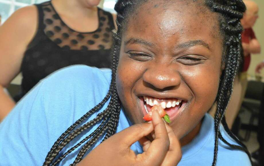 Ahanya Goureige laughs while eating a strawberry during the Family & Childrens Agency ASPIRE program summer lawn party on Tuesday. Photo: Alex Von Kleydorff / Hearst Connecticut Media / Norwalk Hour