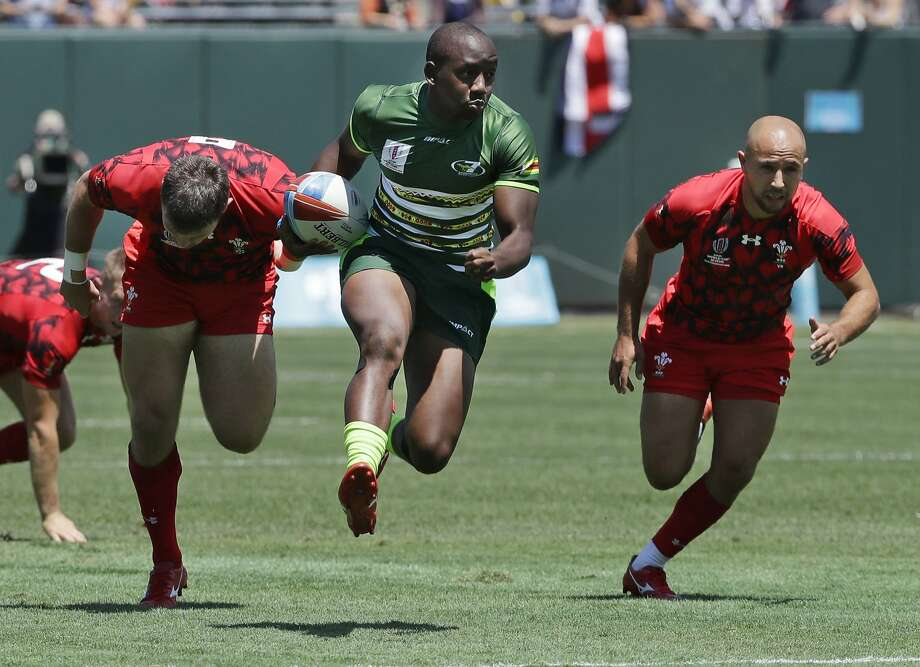 Zimbabwe's Tafadzwa Chitokwindo, center, runs away from Wales players to score during a first-round match Friday. Photo: Jeff Chiu / Associated Press
