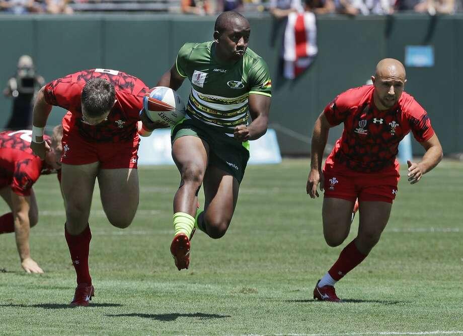 Zimbabwe's Tafadzwa Chitokwindo, center, runs away from Wales players to score during a first-round match Friday. Photo: Jeff Chiu / Associated Press