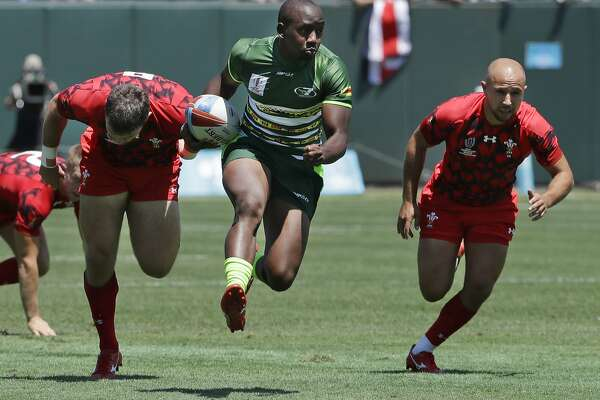 Zimbabwe's Tafadzwa Chitokwindo, center, runs away from Wales players to score during the Rugby Sevens World Cup in San Francisco, Friday, July 20, 2018. (AP Photo/Jeff Chiu)