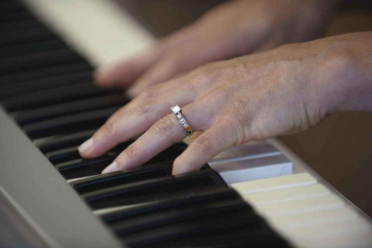 """Constanza Roeder, CEO of the non-profit Hearts Need Art, plays the piano as she sings """"Oceans."""" Roeder wheels the keyboard throughout the cancer unit at Methodist Hospital, offering songs to patients."""