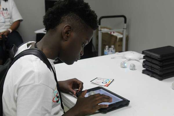 Tyler Dixon, a student at Sloan STEM+Arts camp, demonstrates his programming skills at The Luke Church in Humble on Friday, July 20.