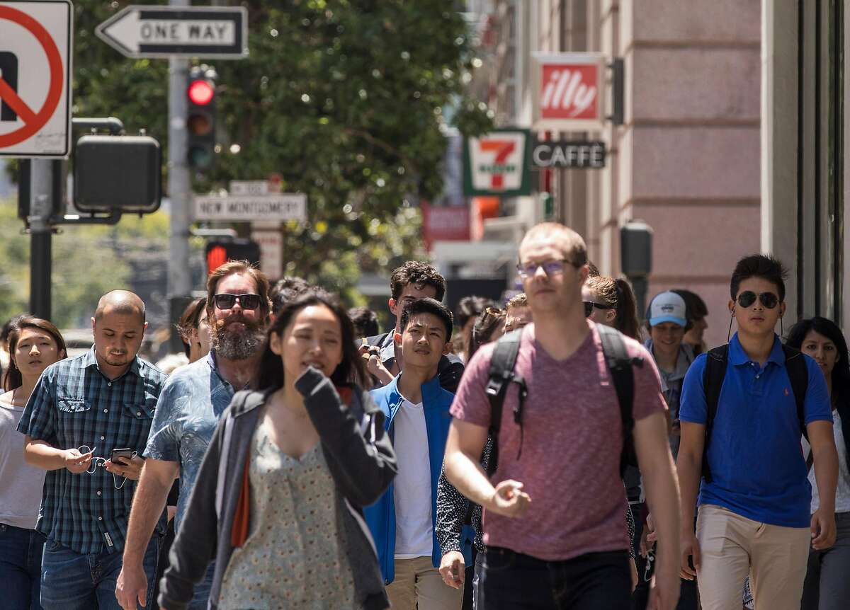 Dozens of San Francisco workers, residents and tourists make their way down Mission Street at New Montgomery in the South of Market district of San Francisco, Calif. Friday, July 20, 2018.