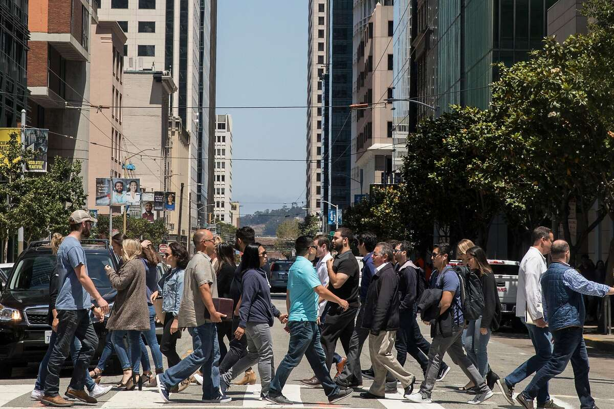 Dozens of San Francisco workers, residents and tourists cross Mission Street at New Montgomery in the South of Market district of San Francisco, Calif. Friday, July 20, 2018.