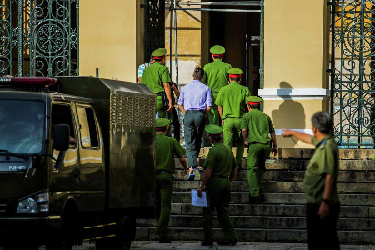 American-Vietnamese citizen William Nguyen is escorted by policemen to a courtroom for his trial in Ho Chi Minh City on July 20, 2018. He was convicted and released. AFP/Getty Images