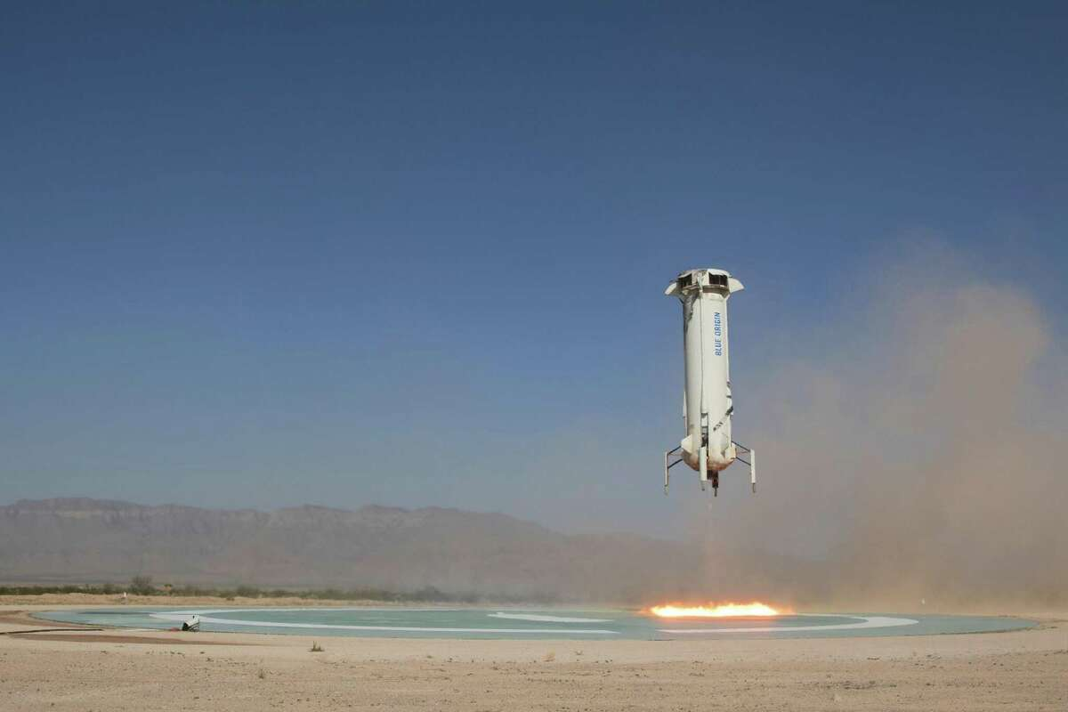 In this photo provided by Blue Origin, The booster of the New Shepard rocket prepares to land in a project called Mission 9 (M9) in western Texas on Wednesday, July 18, 2018. Jeff Bezos' Blue Origin rocket company shot a capsule higher into space Wednesday than it's ever done before. (Blue Origina via AP)