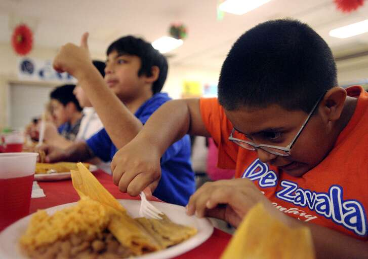Jose Ramirez, 11, a fifth-grade student at De Zavala Elementary School, enjoys a tamale during the 15th annual Bilingual Education Tamalada at the school on Tuesday, Dec. 15, 2009.