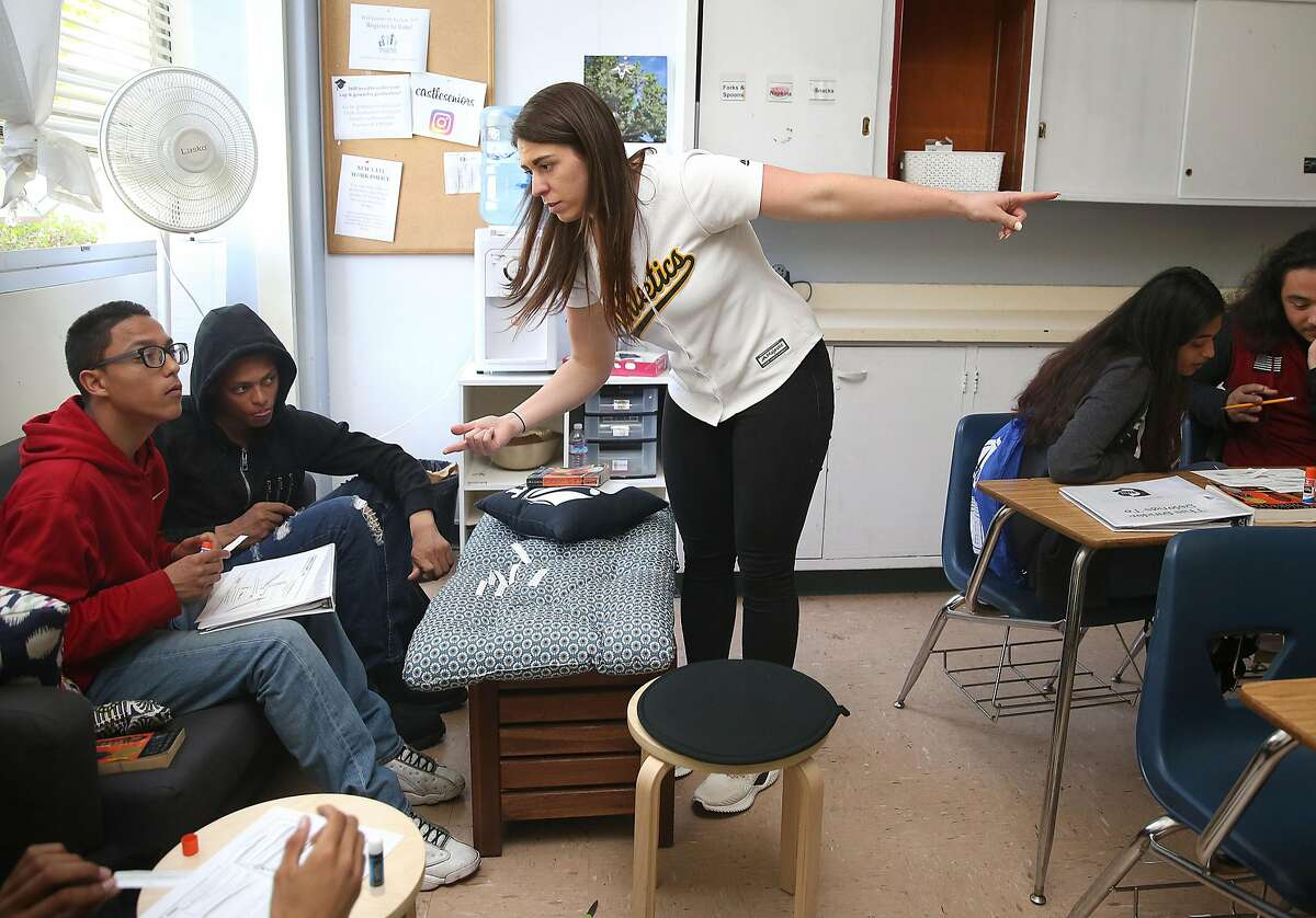 English teacher Ms. Sydney Mulkey (middle) teaches seniors Raymond Sabal (far left) and Kasim Divens (second from left) how to organize events in a plot diagram in class at Castlemont High School on Tuesday, May 8, 2018 in Oakland, Calif. Ms. Sydney Mulkey has 140 junior and senior students this semester.