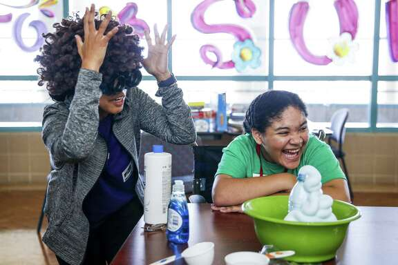 "Shriners Hospital for Children patient Gabriela Borjas, 12, right, laughs with Camp for All 2U staff Natasha Cabalse, left, while watching an ""elephant toothpaste"" chemical reaction July 19, 2018 in Houston. The weeklong camp brings activities such as archery, a petting zoo and fishing to the hospital. (Michael Ciaglo / Houston Chronicle)"