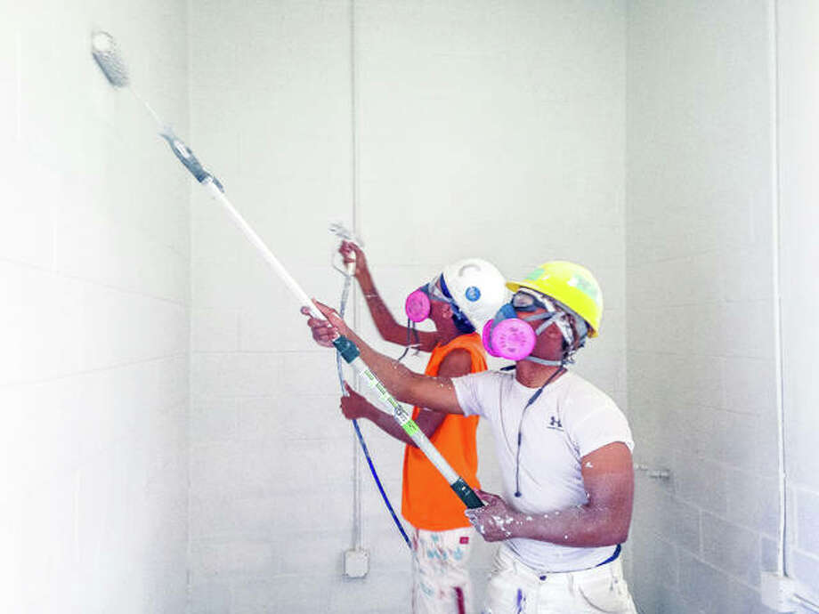 Micah Long, foreground, and Shaniah Cook, both of International Union Painters and Allied Trades pre-apprentice program and St. Louis Job Corps, learn the professional painting trade as they use a spray and roller to paint the cinder blocks inside the future concessions-restroom building at Gordon F. Moore Park in Alton. Photo:       Linda N. Weller | The Telegraph