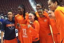 Caroline Hartley from Scarborough, Maine poses with a photo with members of the Connecticut Sun on Friday at Mohegan Sun Arena.
