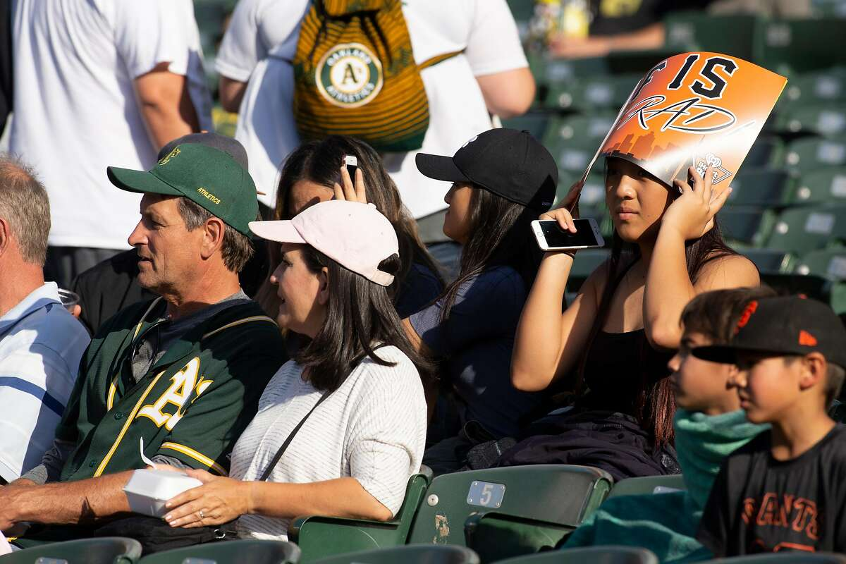 Oakland Athletics and San Francisco Giants fans await the start of a Major League Baseball game, Friday, July 20, 2018 in Oakland, Calif.