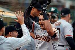 OAKLAND, CA - JULY 20:  Ryder Jones #14 of the San Francisco Giants celebrates in the dugout after hitting a home run against the Oakland Athletics during the fifth inning at the Oakland Coliseum on July 20, 2018 in Oakland, California. (Photo by Jason O. Watson/Getty Images)