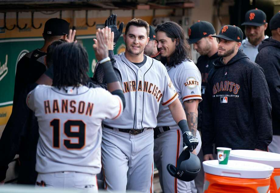 San Francisco Giants Ryder Jones, center, is congratulated by his teammates after hitting solo home run against the Oakland Athletics during the fifth inning of a Major League Baseball game, Friday, July 20, 2018 in Oakland, Calif. Photo: D. Ross Cameron / Special To The Chronicle