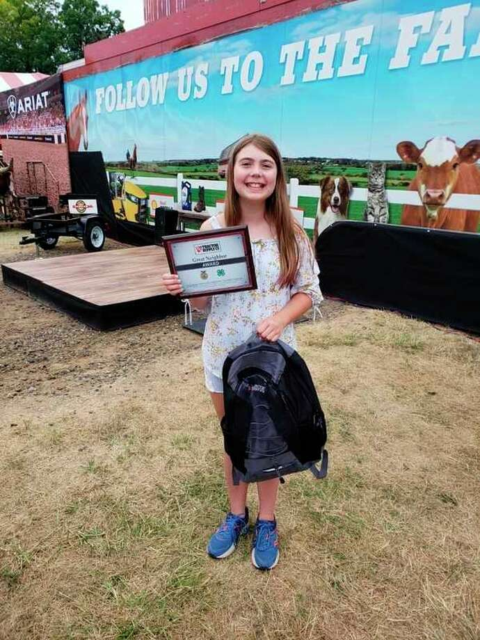 Lauren Geboposes with a commemorative plaque she received as part of Tractor Supply Co.'s 'Great Neighbor' Essay Contest. (Photo provided)