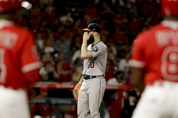 Houston Astros starting pitcher Dallas Keuchel wipes his face after giving up his first hit in the baseball game, to Los Angeles Angels' Justin Upton during the eighth inning in Anaheim, Calif., Friday, July 20, 2018. (AP Photo/Chris Carlson)