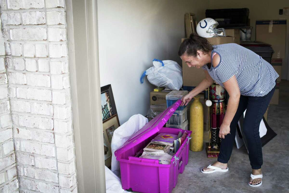 Nicki Thibodeaux opens boxes containing family memories and important paperwork, Friday, Oct. 13, 2017, in Kingwood. Thibodeaux's family was one of the many families who lost their belongings to the dirty flood waters that came in after Hurricane Harvey. ( Marie D. De Jesus / Houston Chronicle )