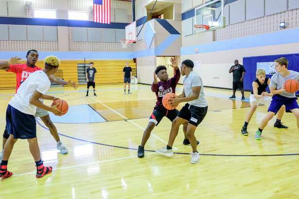 Camp participants work one-on-one drills during the Pearland basketball camp held at Turner High School in Pearland. (Photos by ©Kim Christensen)