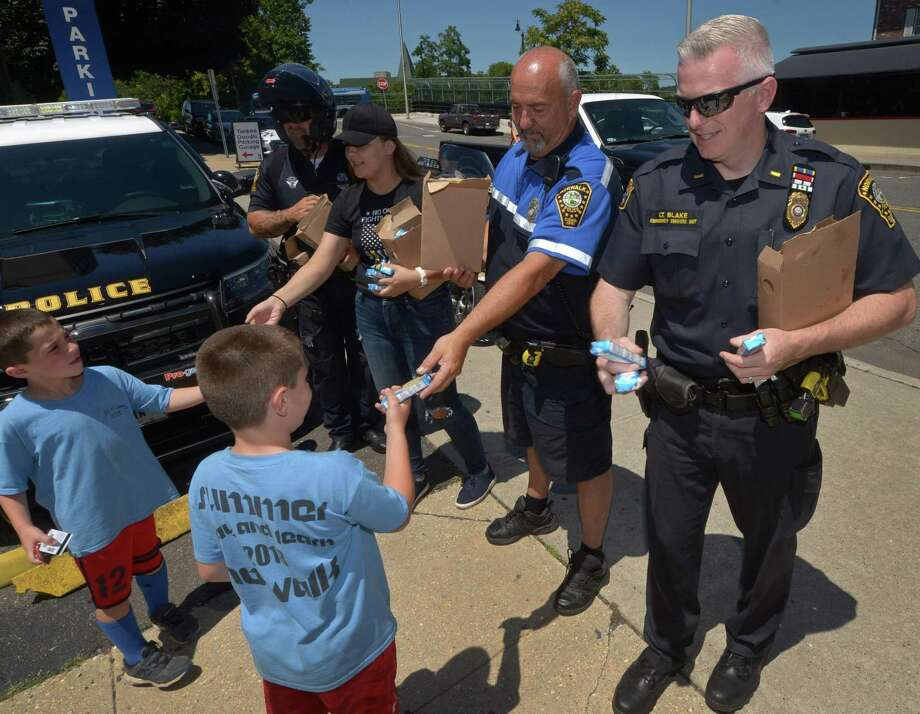 Norwalk Police officer John Zavitz, police intern Alejandra Segura, police officer Russell Oullette and Lieutenant Terry Blake hand out ice cream sandwiches to Norwalk Recreation and Parks Play and Learn campers as part of the 3rd annual Norwalk Police Ice Cream Day Thursday, July 19, 2018 at My Three Sons in Norwalk, Conn. Norwalk Community Police Services and Mr. Frosty's Ice Cream sponsored the event where over 1000 treats were passed to campers from the Recreation and Parks, Carver and children at Norwalk Housing Authority complexes throughout the city. Photo: Erik Trautmann / Hearst Connecticut Media / Norwalk Hour
