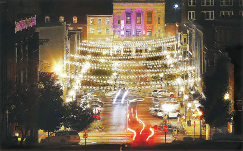 """The lights of cars streak down West Third Street in downtown Alton Wednesday evening under the strings of lights put up by the streaming reality show """"Small Business Revolution — Main Street"""" about a month ago. Photo:       John Badman 