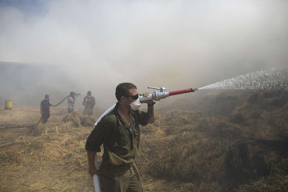 Israeli firefighters and soldiers battle a blaze next to a cow shed in Nahal Oz that was ignited by an incendiary balloon sent over the Gaza border. Photo: Lior Mizrahi / Getty Images