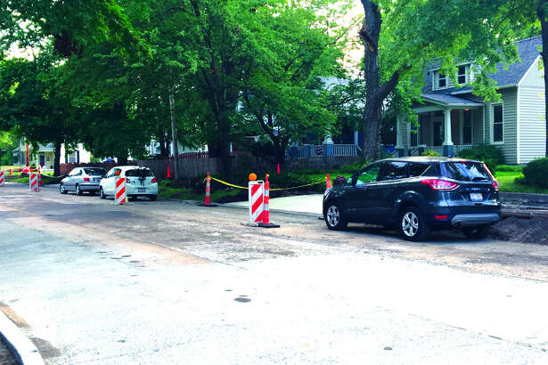 Cars sit parked along the east side of Troy Road on Thursday morning as the resurfacing project from the Leclaire baseball field south to Franklin Avenue continues. New driveways were installed this past week, leaving some residents to park on the closed portion of Troy Road.
