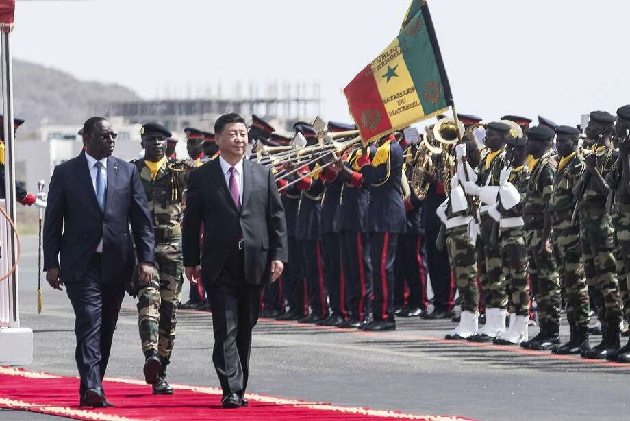Senegal President Macky Sall (left) and Chinese President Xi Jinping inspect an honor guard in Dakar. Xi will also visit Rwanda before attending a summit conference in South Africa. Photo: Xaume Olleros / Associated Press